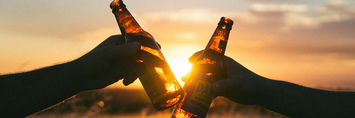 2 people sharing glass bottle root beers at sunset