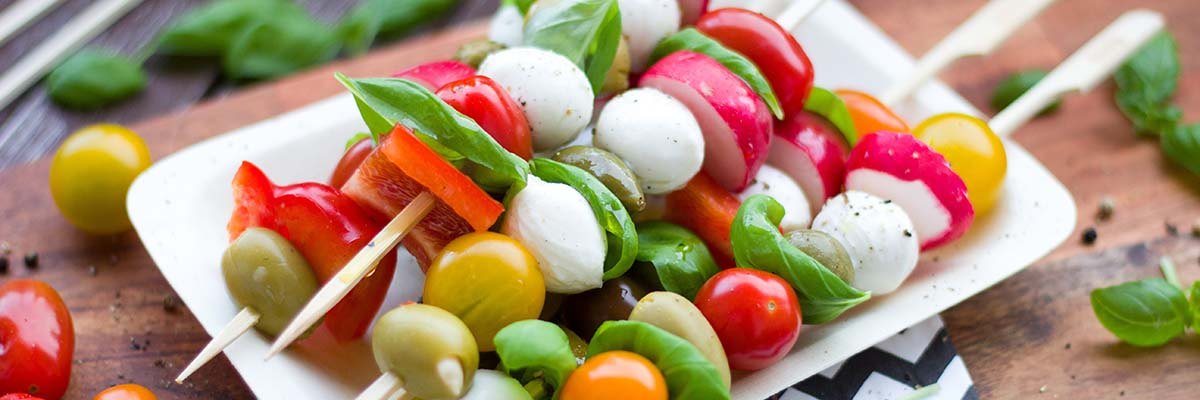 platter with raw vegetable, cheese and olive kabobs
