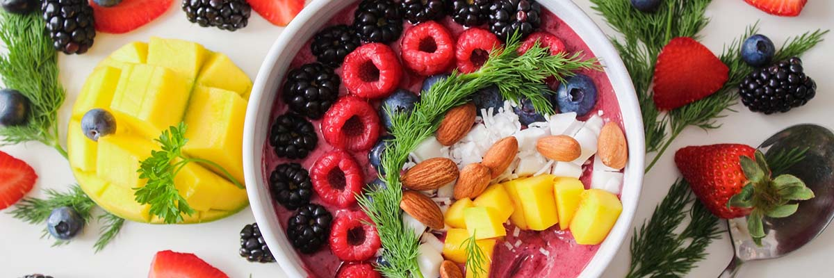 bowl full of fruit and nuts surrounded by more fruit and nuts on a table