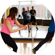 4 people stepping to the right and clapping in a group fitness class