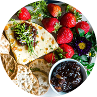various crackers with strawberries, white cheese and blackberry jam on large white rectangular serving dish
