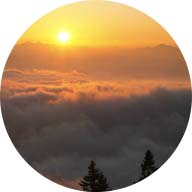 beautiful sunrise over cloud covered mountains below