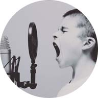 Boy yelling into podcast booth microphone