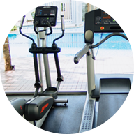 indoor cardio equipment looking out a floor to ceiling winow at an outdoor pool