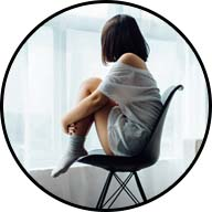 lonely girl with back turned hunched in chair looking out window