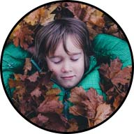 young boy taking a nap in a leaf pile